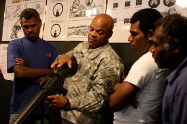 """Staff Sgt. Steve Shepard of the 3rd Infantry Division shows Pacific Islanders how to use a weapon. He welcomed them to his home as part of the Travel Channel's """"Meet the Natives: USA"""" series. The episode is set to air Sunday Dec. 20 at 10 p.m. EST."""