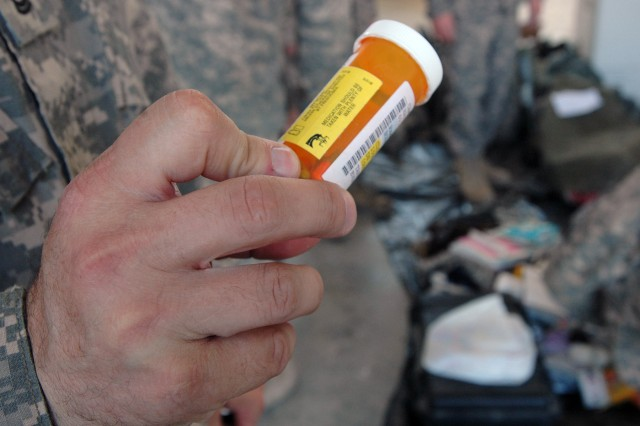 BAGHDAD - Sgt. 1st Class Travis Huggard, the 1st Cavalry Division's customs program manager, reveals a prescription pill bottle found in a Soldier's footlocker that was being inspected to be shipped home, Dec. 11.  All prescription drugs must be hand-carried on the plane.