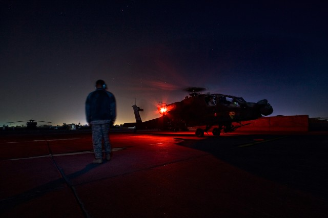 Spc. Jonathan Moore, from Columbus, Ga., an AH-64D Apache attack helicopter crew chief in 4th Battalion, 227th Aviation Regiment, 1st Air Cavalry Brigade, 1st Cavalry Division, stands by to launch Chief Warrant Officer Aaron Fouquette (backseat), fro...
