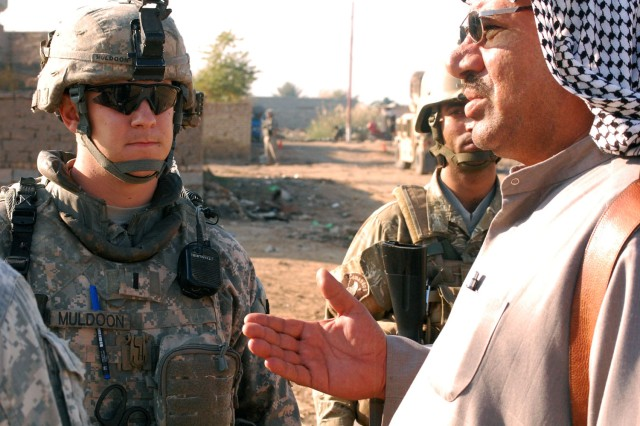 BAGHDAD - Lakeland, Tenn. native, 1st Lt. Patrick Muldoon, a platoon leader assigned to Battery A, 1st Battalion, 82nd Field Artillery Regiment, 1st Brigade Combat Team, 1st Cavalry Division, speaks to a local sheik during a knock and talk mission in Hor al-Bash, Dec. 11. Muldoon and the sheik discussed local security, Sons of Iraq checkpoints, and the growth of the village during their conversation.