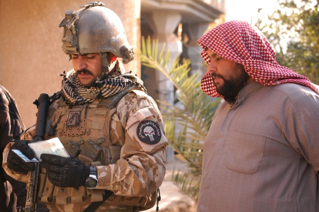 BAGHDAD - An Iraqi Army Soldier assigned to C Company, 22nd Brigade, 6th Iraqi Army Division, checks the identification card of a Hor al-Bash resident during a knock and talk mission, Dec. 11. IA troops partnered with U.S. Soldiers during the mission.
