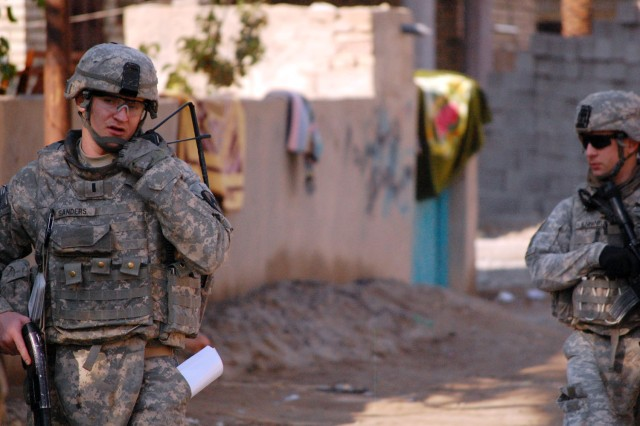 BAGHDAD - Midwest City, Okla. native, 1st Lt. Connor Sanders (left), a platoon leader assigned to Battery A, 1st Battalion, 82nd Field Artillery Regiment, 1st Brigade Combat Team, 1st Cavalry Division, walks through a neighborhood in Hor al-Bash during a joint knock and talk mission, Dec. 11.