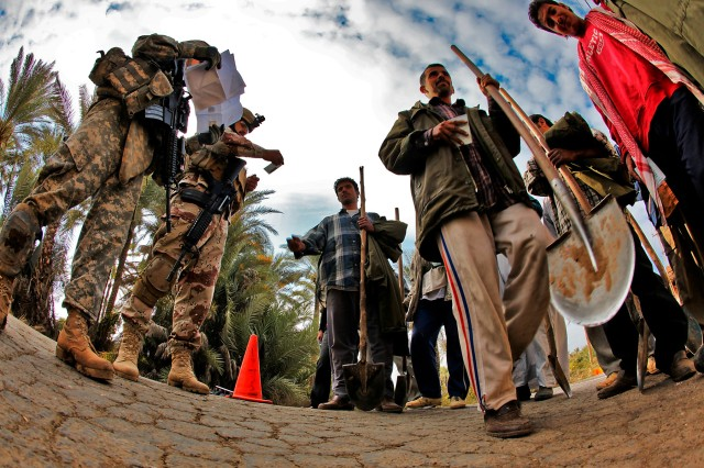 TAJI, Iraq - After taking control of a small intersection, Staff Sgt. Sasaki Palik (left), from Micronesia, a squad leader in 3rd Battalion, 227th Aviation Regiment, 1st Air Cavalry Brigade, 1st Cavalry Division, begins to check the ID cards of personnel passing through here, Dec. 12. The U.S. Soldiers worked with Iraqi Army Soldiers from the 34th IA Brigade, to set up the traffic control point in support of a 1st Brigade Combat Team, 1st Cav. Div., clearing operation.