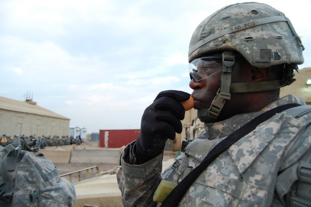 """CAMP TAJI, Iraq -Brookhaven, Miss. native, Sgt. Raymond Nelson, a retransmission team chief assigned to 1st Brigade Special Troops Battalion, 1st Brigade Combat Team, 1st Cavalry Division, kisses his """"battle buddy"""", for good luck, before the Spur Ride kicks off.  Soldiers participating in the Silver Spur Ride on Camp Taji, Dec. 12, were each given an egg to keep safe and protect throughout the competition."""
