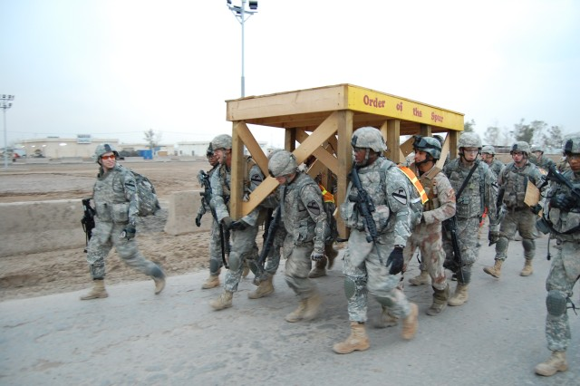 CAMP TAJI, Iraq - Soldiers participating in the Silver Spur Ride on Camp Taji, Dec. 12, carry the Order of the Spur platform to the first obstacle of the challenge.  The Spur Ride lasted nineteen hours and contained nine no-fail tasks that each participant was required to complete.