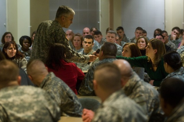 The Chief of Staff of the Army Gen. George W. Casey Jr. gives an Army wife, whose husband is deployed in Afghanistan, the microphone so the audience can hear her question about increasing dwell time during a town hall meeting in Fort Richardson, Alaska, Dec. 14, 2009. Casey said increasing Soldiers' dwell time remains a top-priority and cites the fact that the Army has increased by 70,000 since 2003 as a contributing factor which has helped.