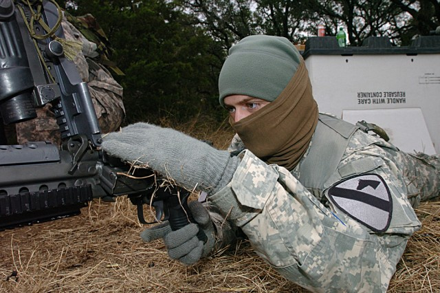 Sgt. Eric Scott, of Jonesborough, Tenn., assigned to Co. B, 2nd Battalion, 7th Cavalry Regiment, prepares to load a weapon Dec. 4, during his unit's spur ride on Fort Hood, Texas.