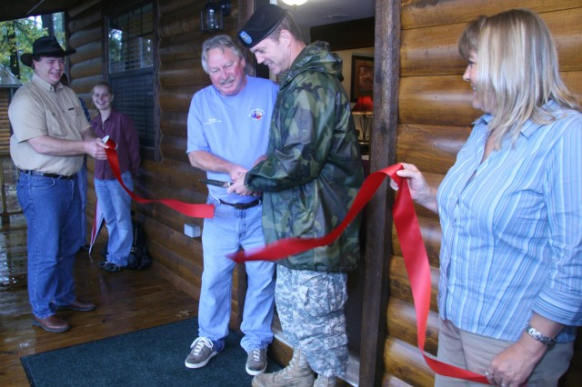 RRAD Commander Col. Daniel G. Mitchell (center) cuts the ribbon to the new cabin with Ricky McClaran, recreational specialist, during the ceremony on October 22.