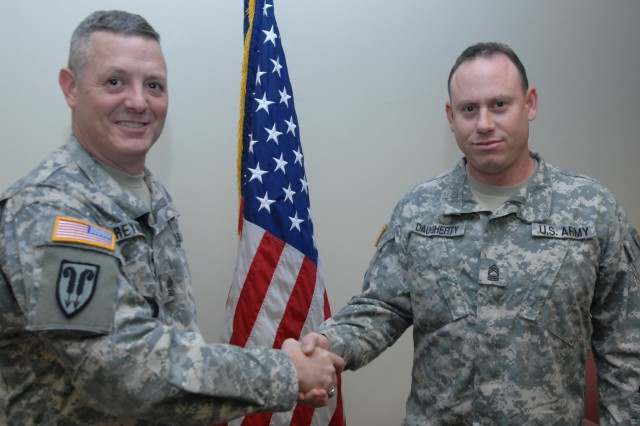 Master Sgt. Cassey Daugherty (left), is congratulated by Sgt. Maj David Reynolds after his reenlistment ceremony on Nov. 24. Daugherty's indefinite reenlistment contract is the second longest in Army history at 216 months (the longest being 224), and is the longest signed at Fort Lee.