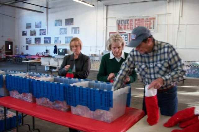 Linda Tippins and Jan and Jim Morgan stuff Christmas stockins for Soldiers with the 402nd Army Field Support Brigade in Balad, Iraq. Commander Lt. Col. Paul Fiscus' family organized the effort and sent 1,550 packages to Soldiers overseas.