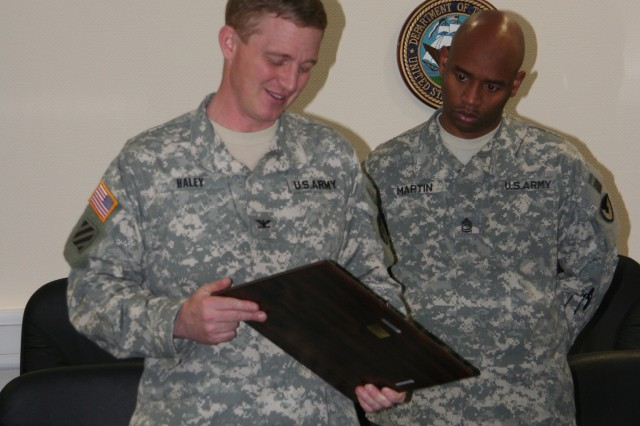 Col. Jack Haley, commander of the 405th Army Field Support Brigade, accepts a plaque from the brigade's non-commissioned officers, including Sgt. First Class Christopher Martin (right) in recognition of his support to the NCO Corps.