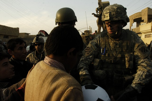 Spartan Commander, Col. Charles E. Sexton, passes out soccer balls during a joint soccer ball donation provided by Spartan Soldiers and Iraqi Security Forces in Mosul, Iraq, Dec. 11.
