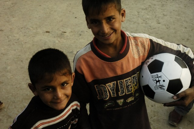 Two children smile after receiving a soccer ball from 2nd Heavy Brigade Combat Team, 3rd Infantry Division Soldiers and Iraqi Security Forces in Mosul, Iraq, Dec. 11.