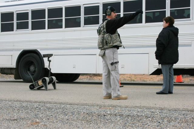 Mark Frye, center, controls a suspected High-Value Target (the bus driver - name not known), right, as she has her picture taken by the Small, Unattended Ground Vehicle (robot) on the left.  The photo was then sent to higher headquarters for verification.