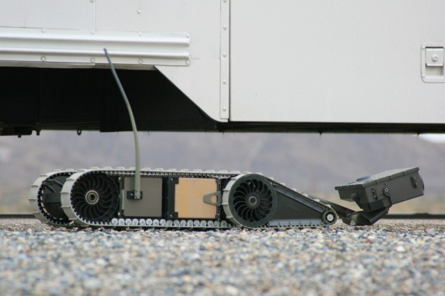 A Small, Unmanned Ground Vehicle in its lowest, ground-hugging position, takes photos of what is under a bus during a Common Controller demonstration at White Sands Missile Range.