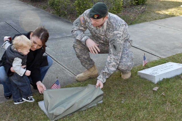 Lindsey Bessa, left, widow of Staff Sgt. Jeremy E. Bessa, Operational Detachment Alpha 3123, 1st Battalion, 3rd Special Forces Group, and son Carson uncover the memorial stone dedicated in her husband's honor at the 1st Bn. Headquarters, Dec. 2. Assisting is Staff Sgt. Joshua M. Stephen, Jeremy's former teammate.