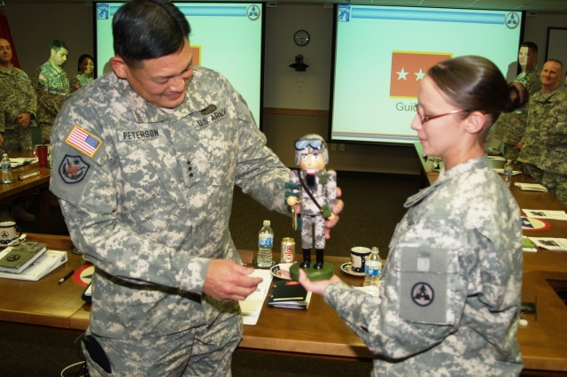 Sgt. Christina DiSano, driver for the 3d Sustainment Command (Expeditionary) commanding general and Brattleboro, Vt., native, presents Lt. Gen. Joseph Peterson, U.S. Army Forces command deputy commanding general and Honolulu, Hawaii, native, a nutcracker in appreciation from the command during his visit Tuesday, Dec. 15. During his visit, Peterson participated in briefings with the intent of identifying and discussing and issues identified during the stages of the Army Force Generation Model. (U.S. Army photo by Spc. Michael Behlin)