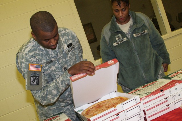 Sgt. 1st Class Anthony Knox, a Soldier with the United States Army Recruiting Command, and Master Sgt. Lerissa D. Wilson, the master chaplain assistant for the 3rd Sustainment Command (Expeditionary), and Lynchburg, Va., native, organize pizzas before starting a Christmas party at the Sunrise Children's Home Dec. 16. (U.S. Army Photo by Spc. Amanda Tucker)