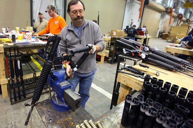Donald Packer swaps out an M-16 rifle stock for a collapsible M-4 stock as part of the US Army Small Arms Readiness Evaluation Team 's restoration project of rifles used in the basic training program.