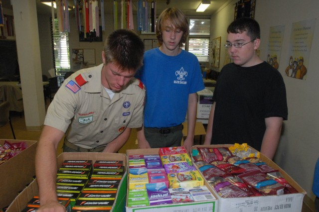 Toby Bledsoe does a quick inventory of a box of drink mixes before preparing it for shipment to Iraq. Bledsoe, of Boy Scout Troop 135 at Hickam Air Force Base, sent more than 400 pounds of non-perishable items to Soldiers of the 558th Military Police Company as part of his Eagle Scout project. Also pictured are Conner Dooley, center, and Brian Gellert.