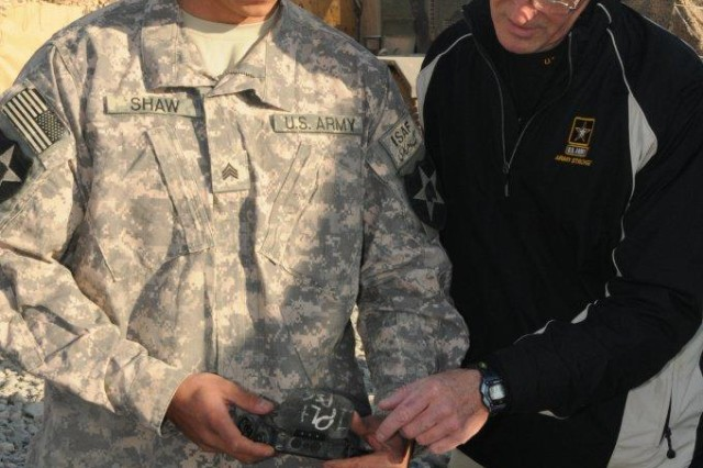Sgt. Harlen D. Shaw, A Company, 52nd Infantry Regiment, Brigade Special Troops Battalion, 5th Stryker Brigade Combat Team, 2nd Infantry Division, gives a demonstration of the Land Warrior system to Secretary of the Army John McHugh at Kandahar Airfield, Afghanistan, Dec. 15, 2009.