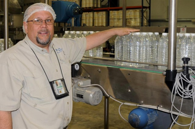 James G. Lalonde, the site manager for the Oasis International Waters water purification facility at Contingency Operating Location Adder, Iraq, and a Clio, Mich., native, demonstrates the system used to purify water, Nov. 11 in the Oasis facility at COL Adder.