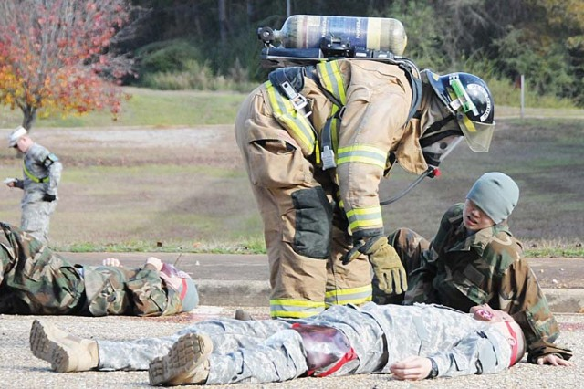 A Fort Rucker Fire Department member checks the condition of mock wounded or dead Soldiers after a simulated terrorist attack at the intersection of Third Avenue and Minute Man Street Dec. 10.