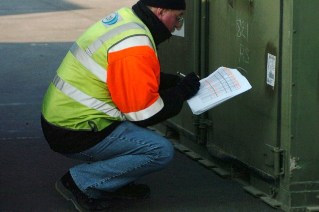 A civilian contractor at the port of Antwerp, Belgium, checks the manifest for a container to be shipped as part of the 172nd Infantry Brigade's redeployment. The operation at the port of Antwerp was a combined mission between the 838th Transportation Battalion, civilian contractors and the 21st Theater Sustainment Command.