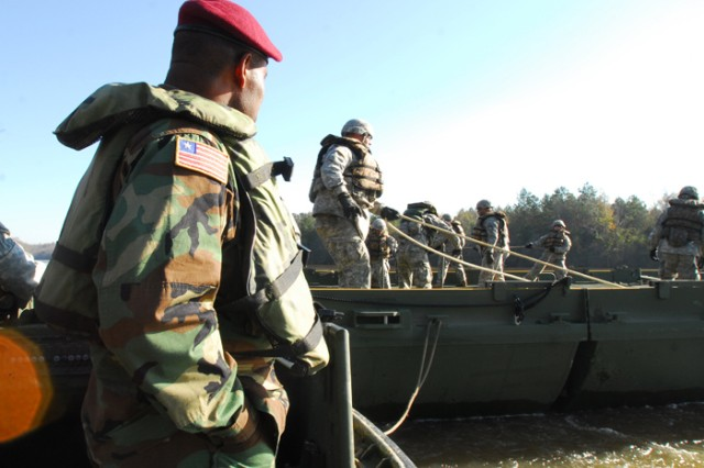 Armed Forces of Liberia Sgt. Maj. Awofeso Bamidele observes Soldiers with the 11th Engineer Battalion construct a bridge Thursday on the Chattahoochee River at Fort Benning.