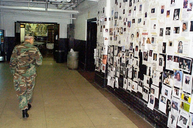 A National Guard member at Manhattan's Lexington Avenue Armory walks by a wall covered with photographs of missing persons after the 9/11 attacks in New York City.  Along with 69th Infantry Regiment Guard members dispatched from there to the disaster's rubble piles, tons of supplies were stockpiled at the armory and hundreds of aid workers were stationed there to give assistance to thousands of grieving family members.