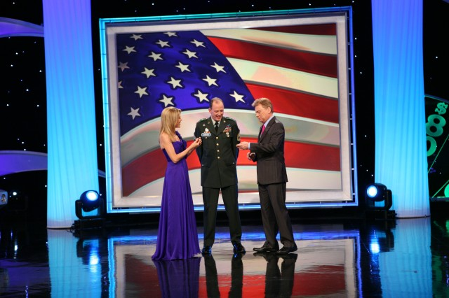 Vanna White (left) and Pat Sajak (right) examine the coins they received from Sgt. 1st Class David Kienzl after the taping of Wheel of Fortune, Oct. 16. The military coin, designed for Company C, 309th Military Intelligence Battalion, Fort Huachuca, Ariz., was the first military coin White ever received.