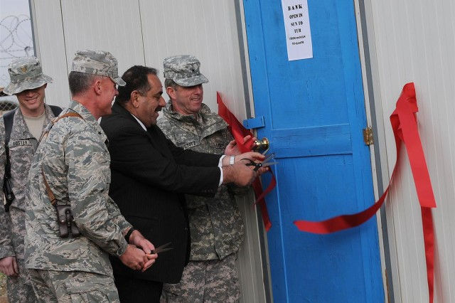Brig. Gen. Paul L. Wentz, commanding general of the 13th Sustainment Command (Expeditionary) out of Fort Hood, Texas, Brig. Gen. Craig A. Franklin, commanding general of the 332nd Air Expeditionary Wing, and Said Saleh Mohammed, the regional manager of Al Warka Bank for the Salah ad Din province, cut the ribbons during the opening ceremony of the Al Warka Bank, Dec. 17 at Joint Base Balad, Iraq.
