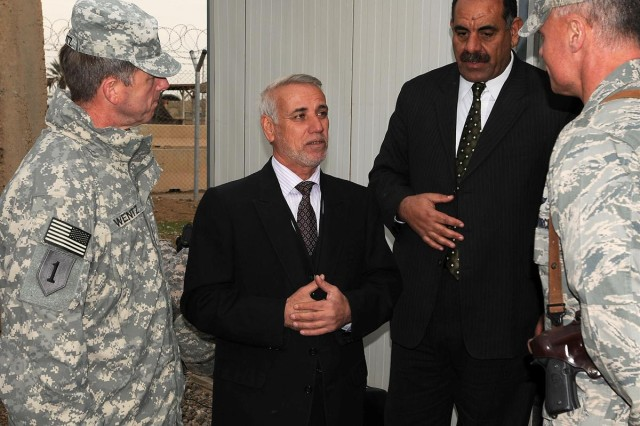 Brig. Gen. Paul L. Wentz, commanding general of the 13th Sustainment Command (Expeditionary) out of Fort Hood, Texas, and Brig. Gen. Craig A. Franklin, commanding general of the 332nd Air Expeditionary Wing, talk to Khalid Almoola, the bank manager, and Said Saleh Mohammed, the regional manager of Al Warka Bank for the Salah ad Din province, after the opening ceremony of the Al Warka Bank, Dec. 17 at Joint Base Balad, Iraq.