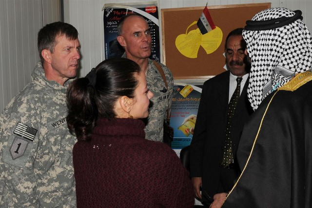 Brig. Gen. Paul L. Wentz, commanding general of the 13th Sustainment Command (Expeditionary) out of Fort Hood, Texas, and Brig. Gen. Craig A. Franklin, commanding general of the 332nd Air Expeditionary Wing, talk to guests after the opening ceremony of the Al Warka Bank, Dec. 17 at Joint Base Balad, Iraq.