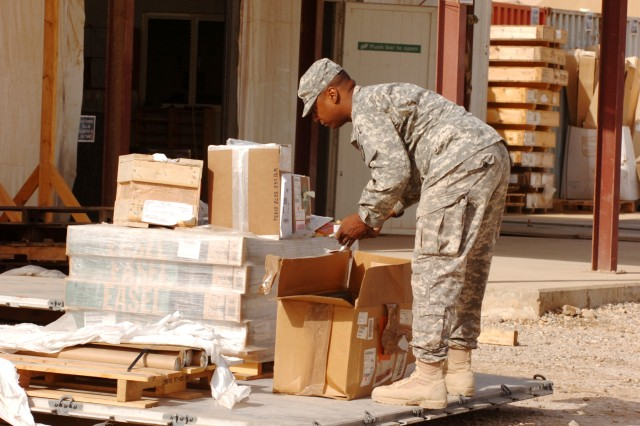 Specialist David English, material handling and storage specialist, Company A, 209th Aviation Support Battalion, Task Force Wings, works breaking down a pallet of supplies at the Supply Support Activities warehouse, Iraq, Nov. 2. (Photo by: Staff Sgt. Mike Alberts 25th Combat Aviation Brigade Public Affairs)