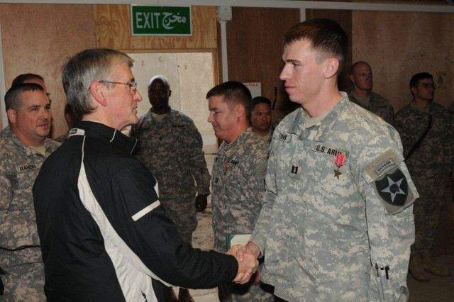 Army Secretary John McHugh shakes hands with Capt. Eric Evans, 5th Battalion, 20th Infantry Regiment, 3rd Stryker Brigade Combat Team, 2nd Infantry Division, following the secretary's presentation of the Bronze Star Medal for the Soldier's meritorious service in support of Operation Iraqi Freedom at Forward Operating Base Warhorse, Diyala, Iraq, Dec. 18, 2009.