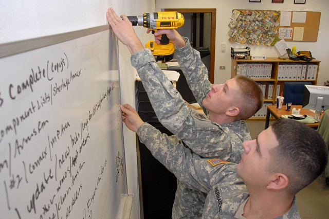 Sgt. Joe Hernandez helps Sgt. John Bobb hang a dry erase board in the supply office of Headquarters Support Company, U.S. Army Africa. The two NCOs are part of a team gearing up for the Army-level Supply Excellence Award.