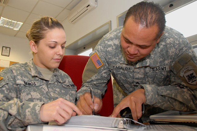 Staff Sgt. Tasha Ramos, 23, who leads Headquarters Support Company, U.S. Army Africa supply office team, signs out equipment to Sgt. Lucky Tagaloa. The supply Soldiers are preparing for an Army-level Supply Excellence Award.