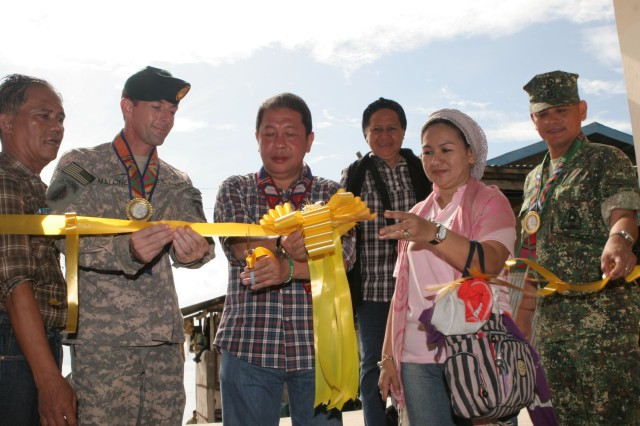 091215-M-6309-035 JOLO, Philippines (Dec. 15, 2009) U.S. Army Maj. Scott Malone, Task Force Sulu commander with Joint Special Operations Task Force - Philippines, holds a ribbon in place while Hon. AbduSakur Tan, governor of Sulu, cuts it.  Also pictured is Nedra Burahan, municipality mayor of Hadji Panglima Tahil and Brig. Gen. Rustico Guerrero, Task Force Comet commander. The ceremony was for the inauguration of an Area Coordination Center, funded in part by JSOTF-P. The ACCs will be used to hold meetings where residents can voice their concerns to improve conditions in the community. (U.S. Marines Corps photo by Sgt Jose E. Castellon/Released)