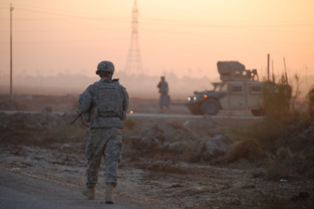 BAGHDAD- Morning light streams across a farm field in Fahama as Soldiers with 1st Brigade Combat Team, 1st Cavalry Division dismount from their vehicles to search the area for caches of weapons and explosive materials.