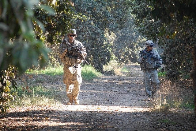 BAGHDAD- Sgt. Chad Haynes (left), a cavalry scout from Austin, Texas, and Staff Sgt. Alfredo Sanchez,  a cavalry scout from Paso Robles, Calif., search fruit groves in Rashidiyah for weapons caches.