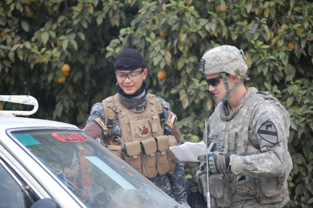BAGHDAD- Sgt. Chad Haynes (right), a cavalry scout from Austin, Texas, and an Iraqi policeman check a motorist's identification card against list at a traffic control point in North Rashidiyah.