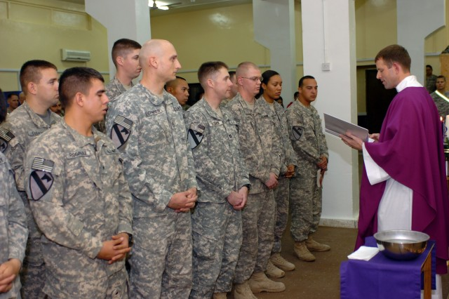 CAMP TAJI, Iraq- Six service members from the 1st Air Cavalry Brigade listen attentively in the front row as Chaplain (Maj.) Tyson Wood (right), from Long Beach Island, N.J., administers their final vows in confirming them as Catholics, in a ceremony held at the Tigris River Chapel, here, Dec. 19.
