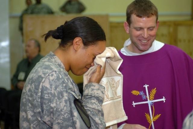 CAMP TAJI, Iraq- 1st Lt. Marjana Mair (left), from Albany, N.Y., smiles as she wipes water from her face after being baptised by Chaplain (Maj.) Tyson Wood (right), from Long Beach Island, N.J., as part of a confirmation ceremony at the Tigris River Chapel, here, Dec. 19. Mair was also confirmed and received her first communion as part of her conversion to Catholicism.