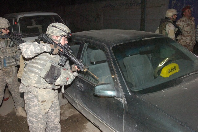 BAGHDAD- Spc. Mario Hineman, a native of Sierra Vista, Ariz., conducts a brief search on a parked vehicle during a combined night patrol in Sadr City, Dec. 16.