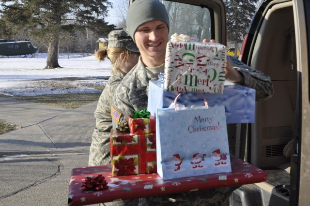 Sgt. Joshua Seil unloads gifts at the North Dakota Veterans Home in Lisbon, N.D. Guard members delivered Christmas gifts as part of an annual holiday event honoring the residents of the home.