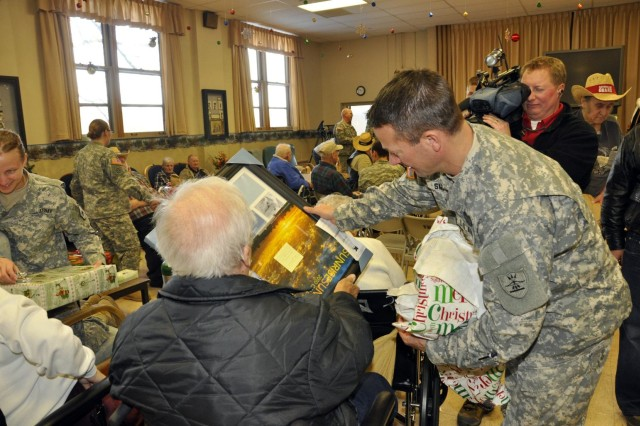 Lt. Col. Rick Smith helps a veteran unwrap his gifts at the North Dakota Veterans Home in Lisbon, N.D. The Guard members delivered Christmas gifts as part of an annual holiday event honoring the residents of the home.
