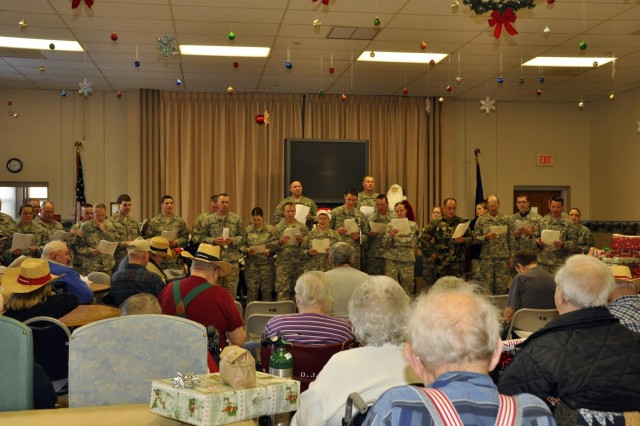 North Dakota National Guard Soldiers and Airmen serenade veterans with Christmas carols. The caroling was part of the festivities of an annual holiday event honoring the residents of the home.