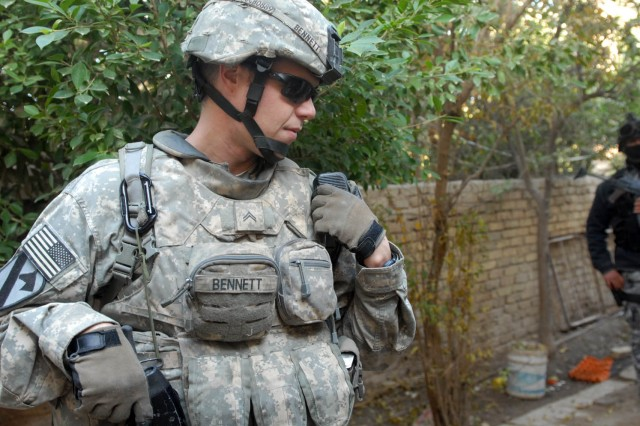 BAGHDAD - St. Mary's County, Md. native, Cpl. Timothy Bennett, a team leader assigned to the 1st Squadron, 7th Cavalry Regiment, 1st Brigade Combat Team, 1st Cavalry Division, communicates with his platoon leader, Dec. 11, outside Joint Security Station Istiqlal.