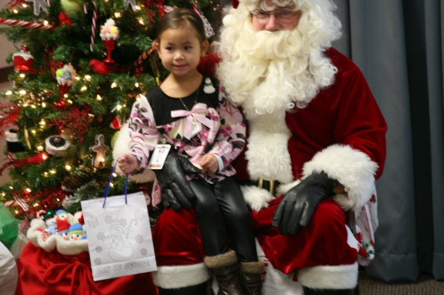 Carol Spears, daughter of USASMDC/ARSTRAT Inspector General employee Ben Spears, sits on Santa's lap.